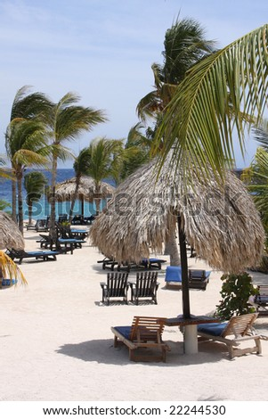 Caribbean beach parasols and sun chairs - stock photo