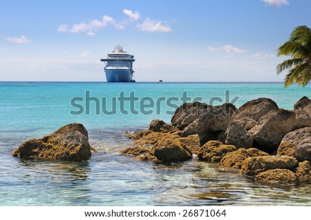 Caribbean Beach with rocks and cruise ship in background - stock photo