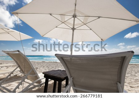 Caribbean beach with sun umbrellas and beds  - stock photo
