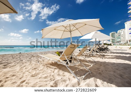 Caribbean beach with sun umbrellas and beds  - stock photo
