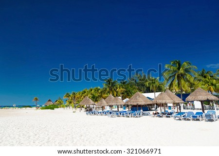 Caribbean beach with sun umbrellas and beds, Cancun, Mexico