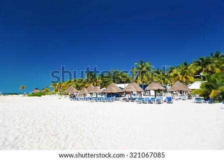 Caribbean beach with sun umbrellas and beds, Cancun, Mexico  - stock photo