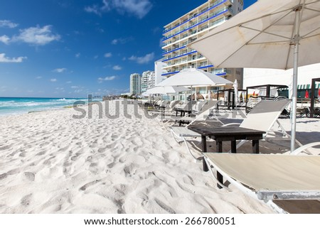 Caribbean beach with sun umbrellas and beds. Vacation concept  - stock photo