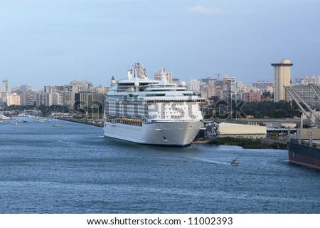 Caribbean Cruise Ship docked in the port of San Juan,City skyline in background - stock photo