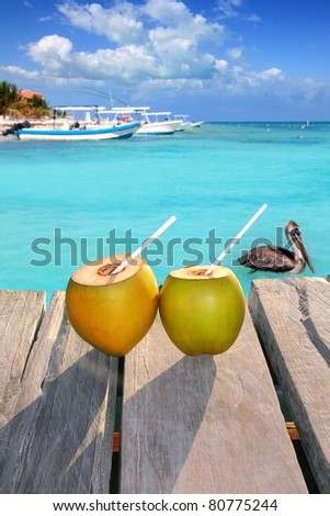 Caribbean fresh coconuts cocktail on pier with pelican in turquoise sea [Photo Illustration]