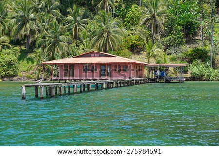 Caribbean house with dock over the water and tropical vegetation on the land, Bocas del Toro, Panama, Central America - stock photo