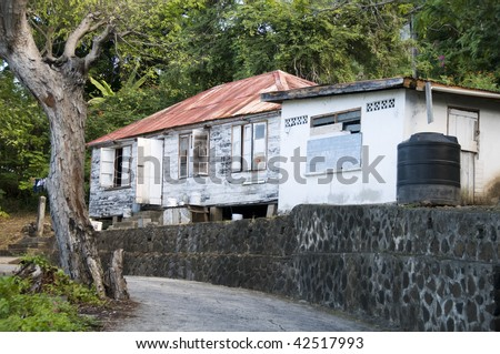caribbean island house with zinc roof and plastic water tank cistern bequia st. vincent and the grenadines - stock photo