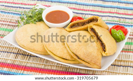 Caribbean Jerk Beef Patty - Jamaican spicy minced jerk beef with onions and peppers in short crust pastry served with spicy sauce and scotch bonnet chillies. - stock photo