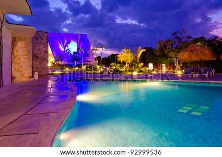 Caribbean resort swimming pool at night. - stock photo