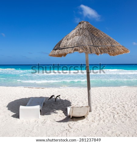 Caribbean sea coastline with grass sun umbrella and wooden beach beds. Vacation concept