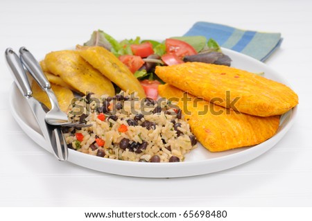 Caribbean style meal with gallo pinto, meat patties and fried plantain. - stock photo