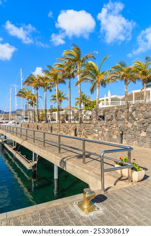 Caribbean style port with tall palm trees in Puerto Calero, Lanzarote island, Spain - stock photo