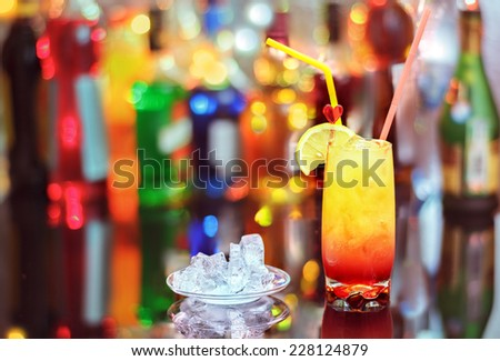 Caribbean sunset cocktail on the bar on the blur background.