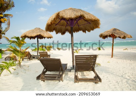 Caribbean tropical white sand beach with umbrellas and chairs - stock photo