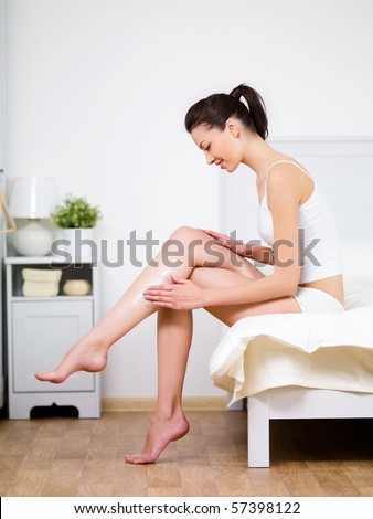 Caring about woman's leg with moisturizing cream by young beautiful woman sitting on a bed at home - stock photo