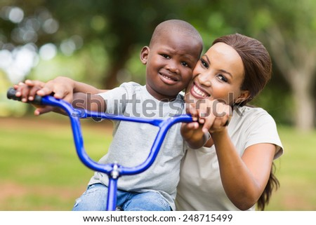 caring african american woman helping her son to ride a bike in park - stock photo