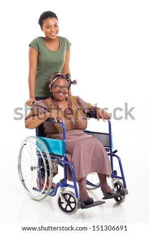 caring african daughter pushing senior mother on wheelchair over white background - stock photo