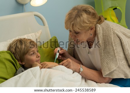 Caring aged grandmother checking her grandson's temperature  - stock photo