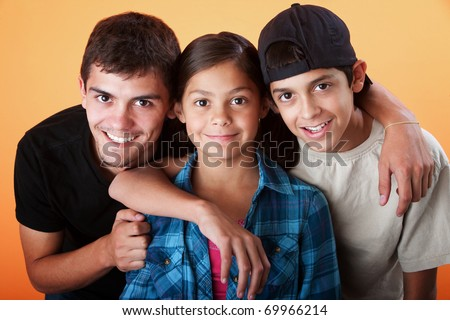 Caring brothers with their sister smiling on orange background - stock photo