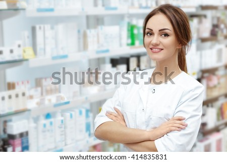 Caring customers with a smile. Horizontal portrait of a beautiful pharmacist smiling to the camera cheerfully posing in the drugstore.  - stock photo