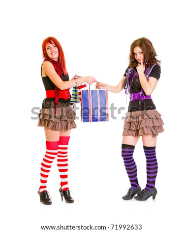 Caring cute girl giving one shopping bag her surprised girlfriend isolated on white - stock photo