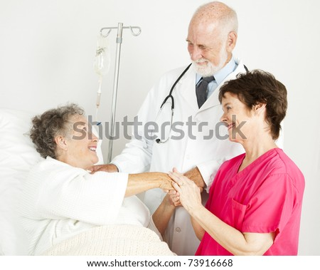 Caring doctor and nurse greeting hospital patient. - stock photo