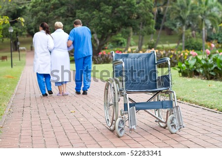 caring doctor and nurse helping senior patient get up from wheelchair and walk - stock photo