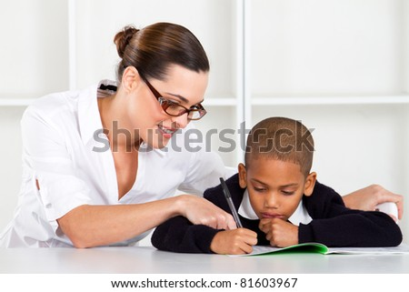 caring elementary teacher helping schoolboy - stock photo