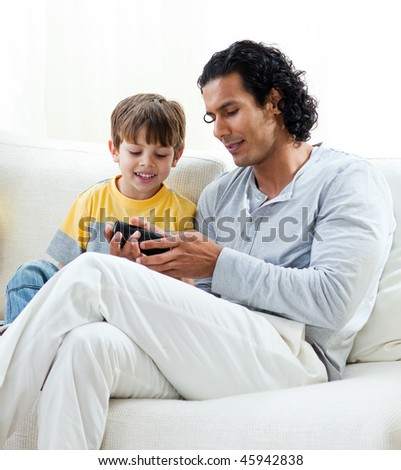 Caring father and his son sitting on a sofa at home - stock photo