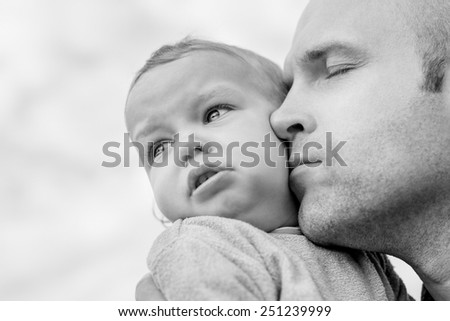 caring father calms toddler son outdoors  ( black and white )  - stock photo