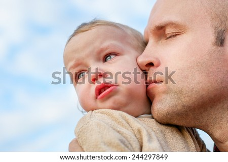 caring father calms toddler son outdoors on the sky background - stock photo