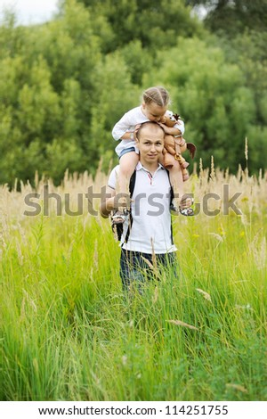 Caring father carrying daughter on his neck while walking outdoors on a meadow - stock photo