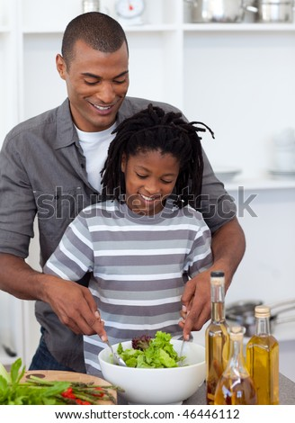 Caring father helping his son cut vegetables in the kitchen - stock photo