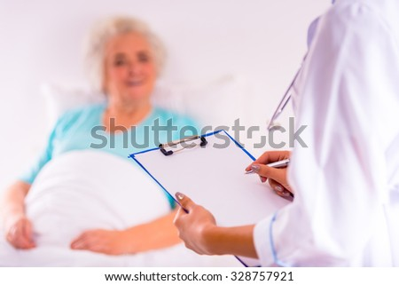 Caring for a sick senior woman in hospital - stock photo