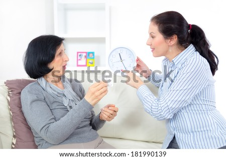 Caring for the elderly. Adult woman giving medicament to mature mother at home