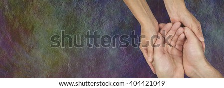Caring for those in need - rustic dark stone effect wide background with a woman's hands cupped around a man's hands depicting a carer  - stock photo