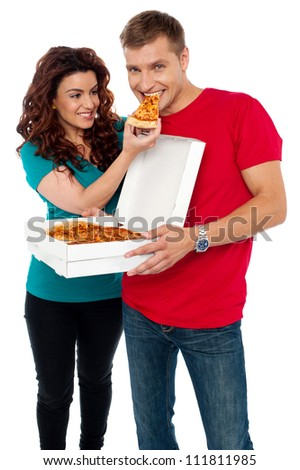 Caring girlfriend making her boyfriend eat pizza. Adorable love couple