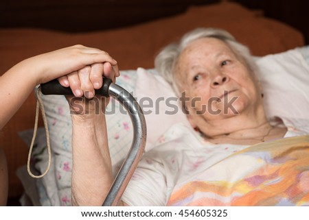 Caring hands holding old lady's hands in bed at home