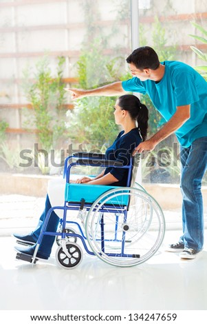 caring husband and disabled wife looking outside window at home - stock photo