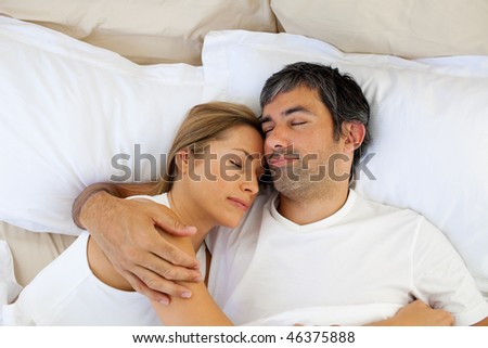 Caring lovers sleeping lying in the bed at home - stock photo