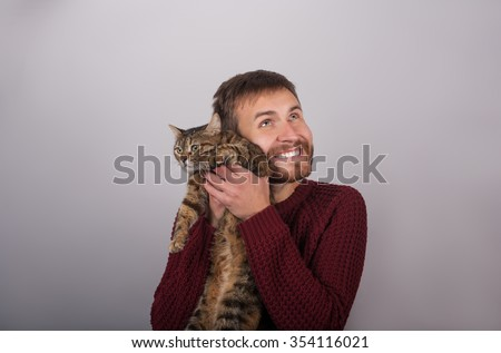 Caring man holding a cat - stock photo