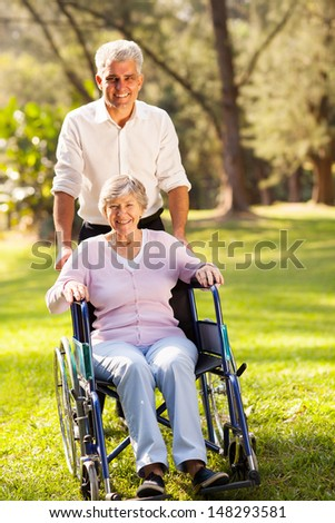 caring mid age son taking disabled senior mother for a walk outdoors in forest