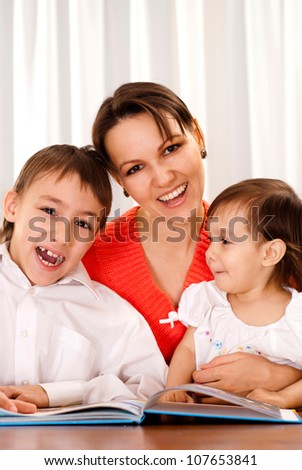 Caring mother decided to read to her children an interesting book on Christmas Eve - stock photo