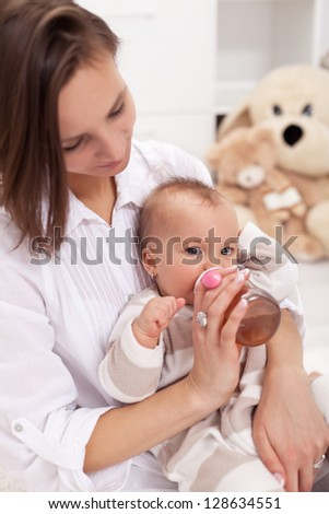 Caring mother feeding baby girl with bottle - stock photo