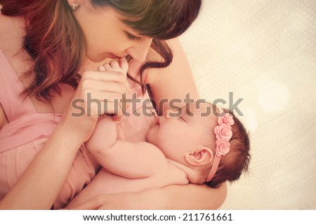 caring mother kissing little fingers of her cute sleeping baby girl, happy family concept - stock photo
