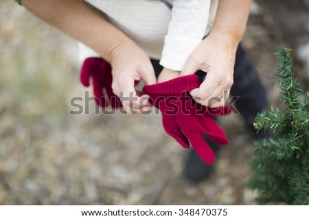 Caring Mother Putting Red Mittens On Child Near Small Christmas Tree Abstract. - stock photo