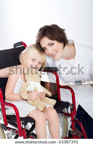 caring nurse and smiling little girl on a wheelchair