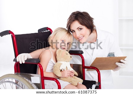 caring nurse and smiling little girl on a wheelchair - stock photo