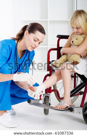 caring nurse bandage little girl's ankle - stock photo