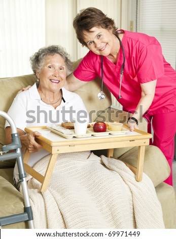Caring nurse brings meal to home-bound senior woman. - stock photo